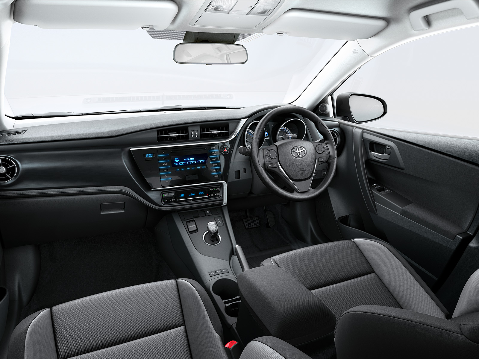 Toyota Auris, interior, leather steering wheel, control panel, gear stick, grey front seats & side of glove compartment in sight, white and grey colour scheme.
