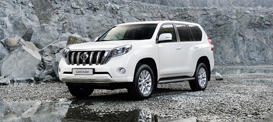 Toyota Land Cruiser, exterior white, in front of grey rocky background.