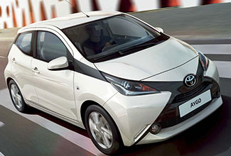 Toyota Aygo, exterior front side view, White, man driving