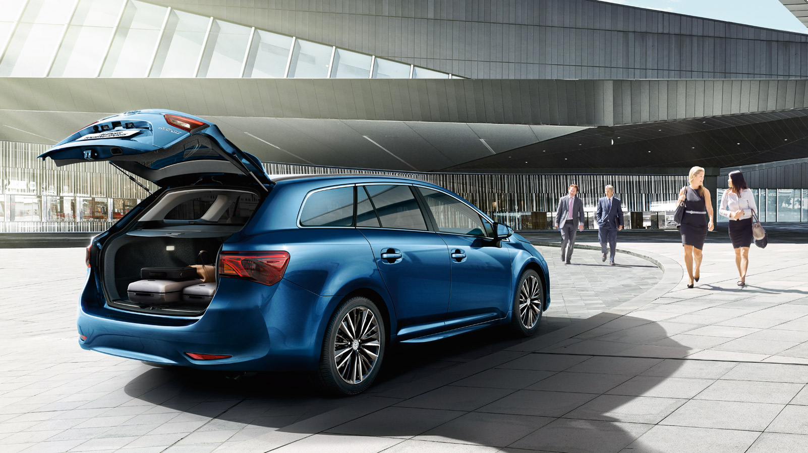 Toyota Avensis exterior, Blue, back side view, open boot with suitcases, daytime shot, women & men walking past