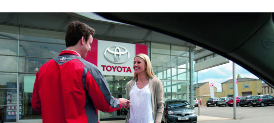 A customer and a Toyota service advsior in front of a Toyota dealership